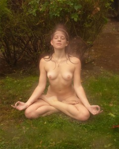Naked woman meditating outdoors on grass